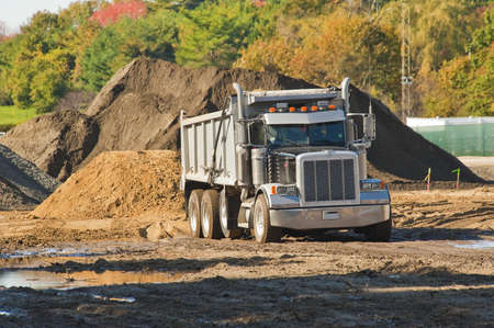 dumps: A dump truck about to unload a pile of dirt at an excavation site