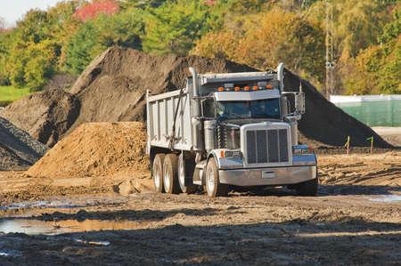 mining truck: Un camión volcado a punto de descargar un montón de tierra en una excavación Foto de archivo