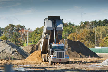 A dump truck is dumping dirt on an excavation site
