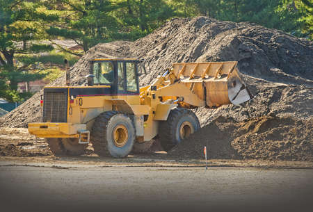 Front end loader moving piles of dirt on a construction site Stock Photo - 11139210