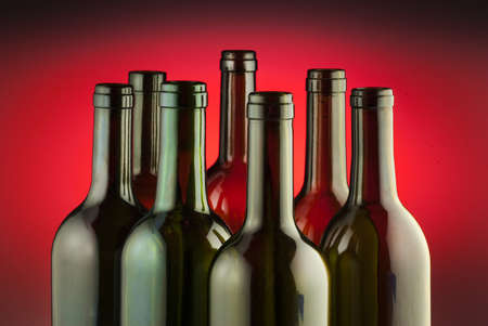 Red wine bottles against a red spot effect background