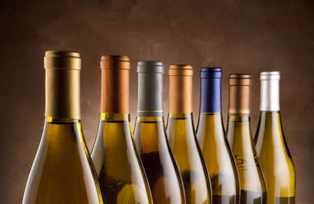 White wine bottles lined up in a row photo