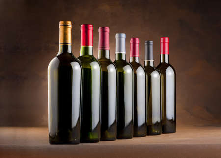 bottle opener: Red wine bottles in a row  on a mottled canvas background Stock Photo