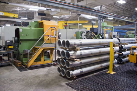 Machine shop interior with manufactured steel tubes in foreground Stock Photo - 12903697