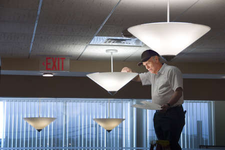 light fitting: Maintenance man changing light bulbs in business office Stock Photo