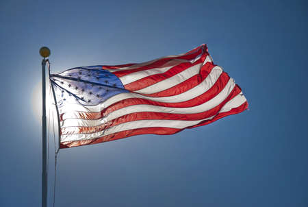 American flag back lit by sun photo