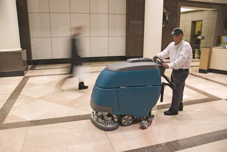 Cleaning floor in office building lobby Stock Photo