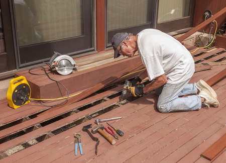 Senior repairing mahogany wooden deck photo