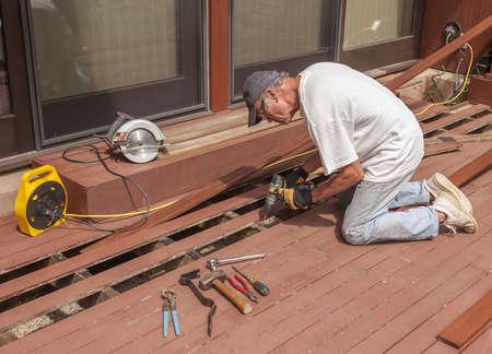 fixing: Senior repairing mahogany wooden deck