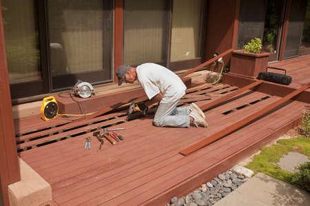Senior repairing mahogany wooden deck