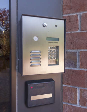 intercom: Electronic door directory and security pad near the front door entrance of a  commercial building
