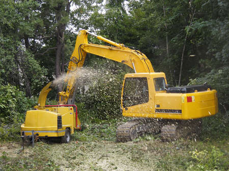 wood agricultural: Commercial wood chipper being fed by a shovel