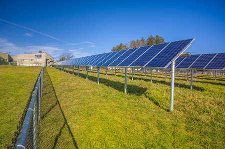 furnish: Solar panels in field with blue sky used to furnish electricity to building Stock Photo