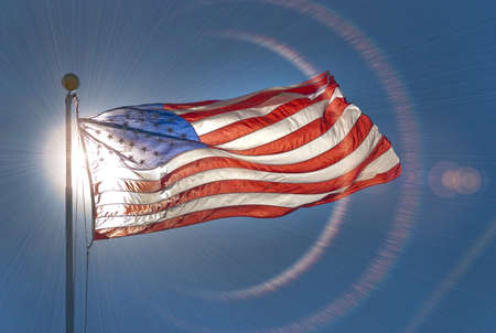 American flag, back lit by the sun, waving in the wind with lens flare Stock Photo - 16913818
