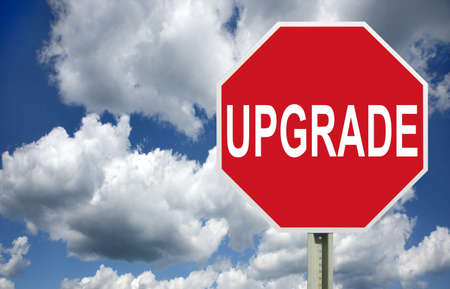 Upgrade road sign in red over clouds, isolated photo