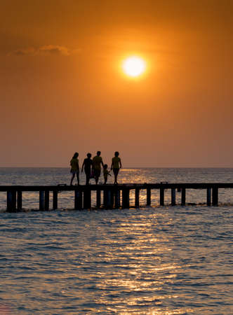 Silhouette of family walking over a bridge at sunset Stock Photo - 17883416