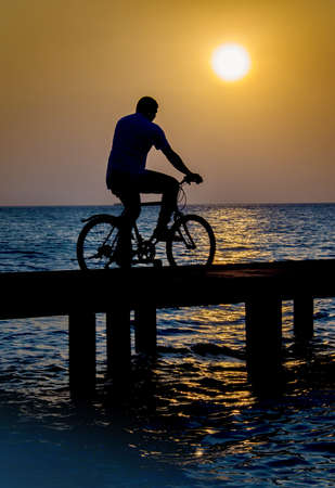 Man on bicycle crossing a bridge at sunset Stock Photo - 17884079