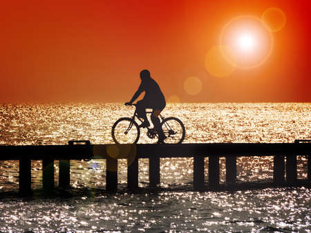 Silhouette of man bicycling across bridge at sunset with lens flare Stock Photo - 18264524
