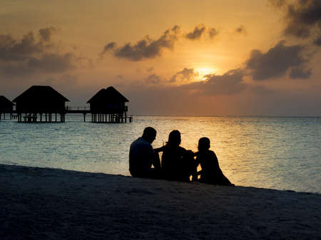 Silhouette of family at sunset on vacation having a drink Stock Photo - 18279065