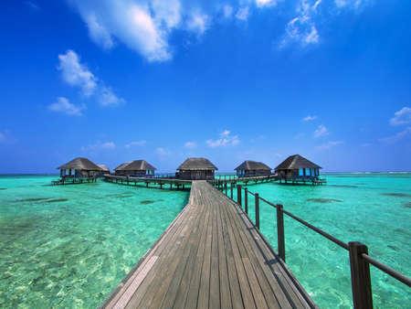 몰디브에서 아쿠아 마린 바다를 덮는 방갈로