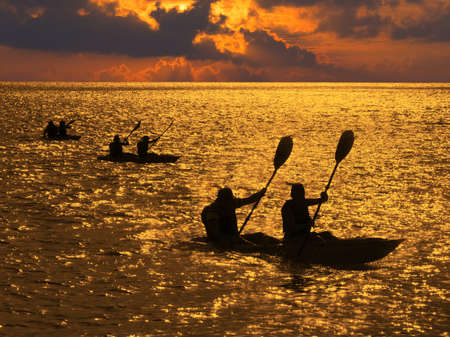 Silhouette of kayakers at sunset Stock Photo - 18279071