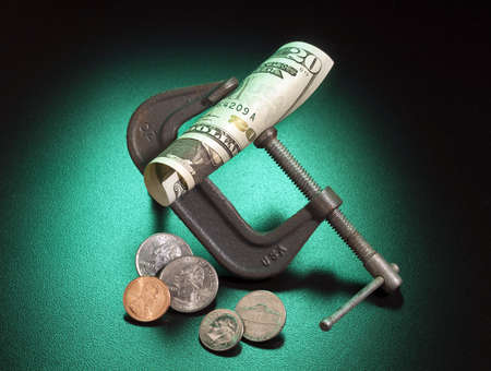 squeeze: Money being squeezed as a metaphor for loss of buying power Stock Photo