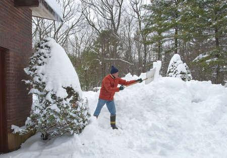 shoveling: Senior man shoveling his walkway after a big snow storm Stock Photo