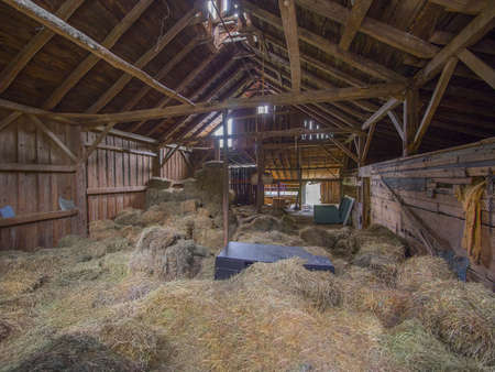 Old post and beam barn interior with hay on the floor