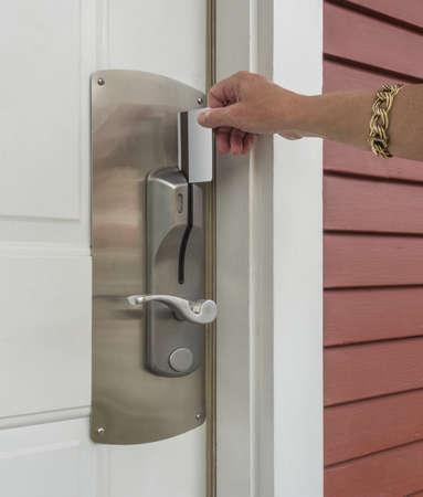Hand inserting a keycard in hotel door lock