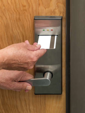 Hand inserting keycard in hotel room door lock