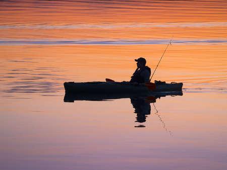 Fisherman kayaking around sunset in tranquil lake photo