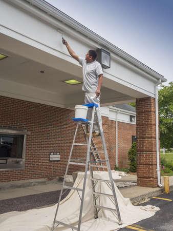 steeplejack: Hispanic man painting soffit of a building