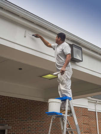 Hispanic man painting soffit of a building
