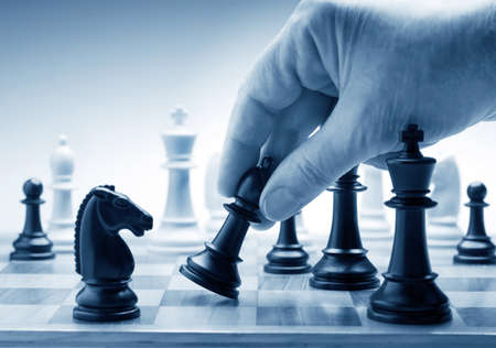 chess board: Hand moving a chess piece on board
