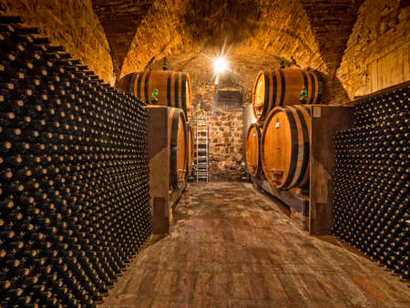 flessen wijn en eiken vaten gestapeld in een wijnkelder