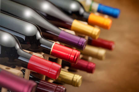 wine bottles stacked in a rack with colorful foil necks Stock Photo