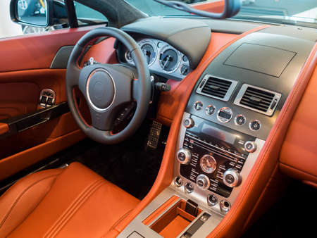 interior cockpit dashboard of an expensive sports car lined in leather and carbon fiber