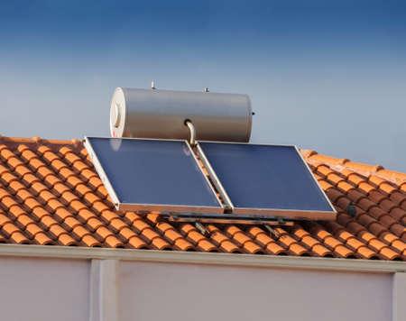Solar water heater on tiled roof house Foto de archivo
