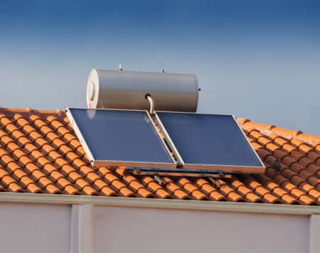 Solar water heater on tiled roof house Archivio Fotografico