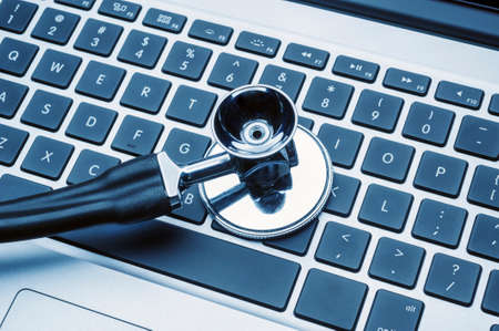 diagnostic tool: close up of stethoscope  on laptop computer keyboard Stock Photo