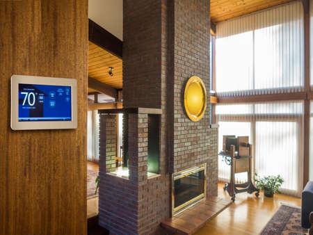 woonwijk: Programmeerbare thermostaat voor de temperatuurregeling in de woonkamer Stockfoto