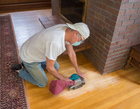 Older man using an electric sander on wood floor Stock Photo