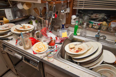 cleaning kitchen: Dirty dishes over flowing in a kitchen sink Stock Photo