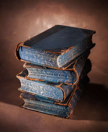 stacked books: stack of old books on a painted canvas backdrop