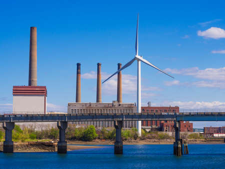 fossil fuel: Eco power wind turbine in the city replacing old style fossil fuel burning plant