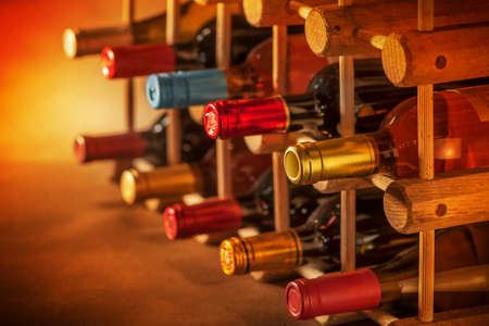 wine bottles stacked on wooden racks shot with limited depth of field Archivio Fotografico