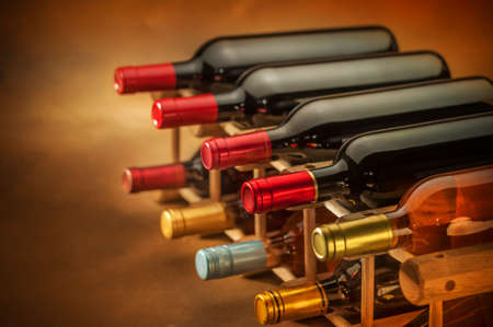 wine bottles stacked on wooden racks shot with limited depth of field Foto de archivo