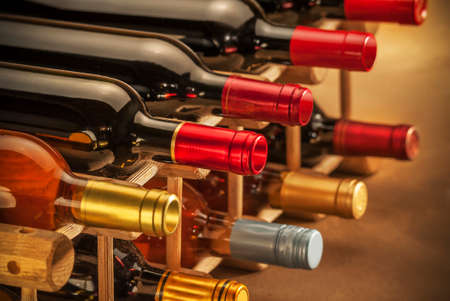 intoxicant: wine bottles stacked on wooden racks shot with limited depth of field Stock Photo
