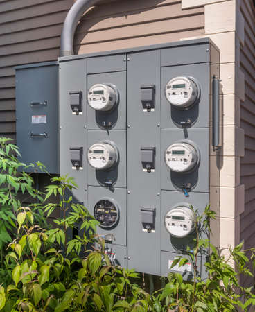 electricity usage meters on the side of a small mall