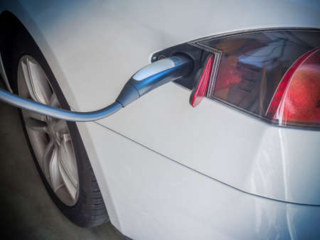 plugged in: Electric Car Being Charged. Charging an electric car with the power supply plugged in Stock Photo